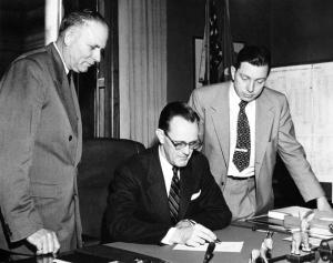 John Hannah observes signing the Michigan State University Bill, 1955. Courtesy On the Banks of the Red Cedar