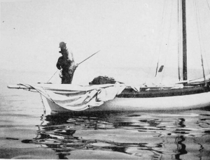 Fishermen in a Mackinaw boat raising their nets. Image Source