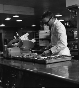 Man prepares meat in the Kellogg Center 1959. Image courtesy of MSU Archives & Historical Collections