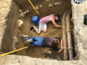 Josh Eads and Kaleigh Perry work to excavate under the large ceramic pipes located along the foundation wall in Unit A.